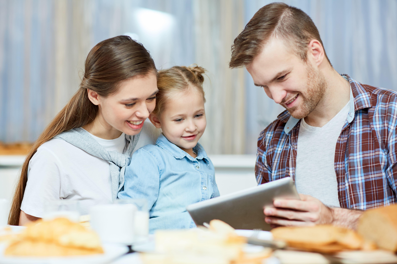 pais com criança, olhando para um tablet